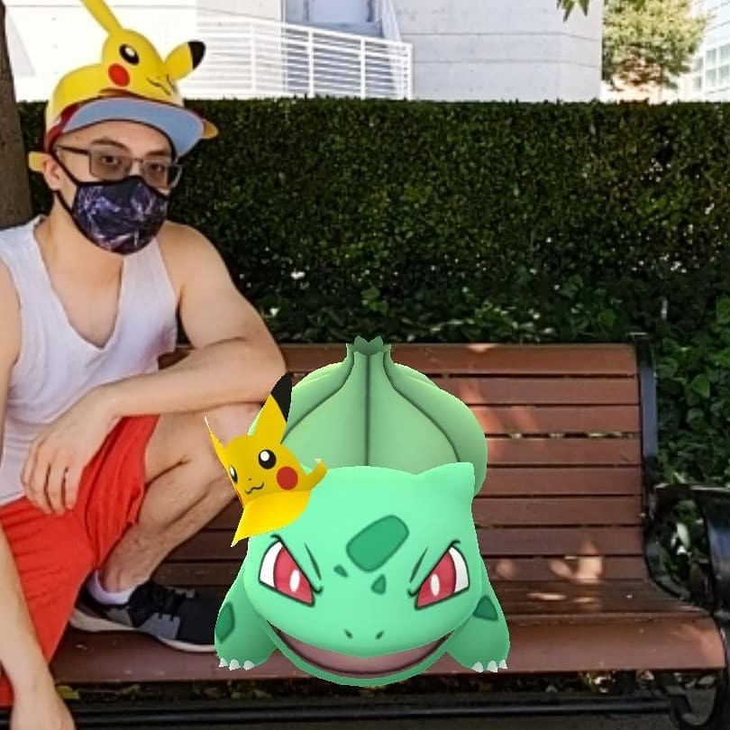 An Asian man posing on a bench with various animated Pokemon.