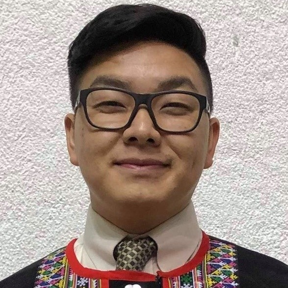 A Hmong man with glasses wearing cultural clothing and smiling.