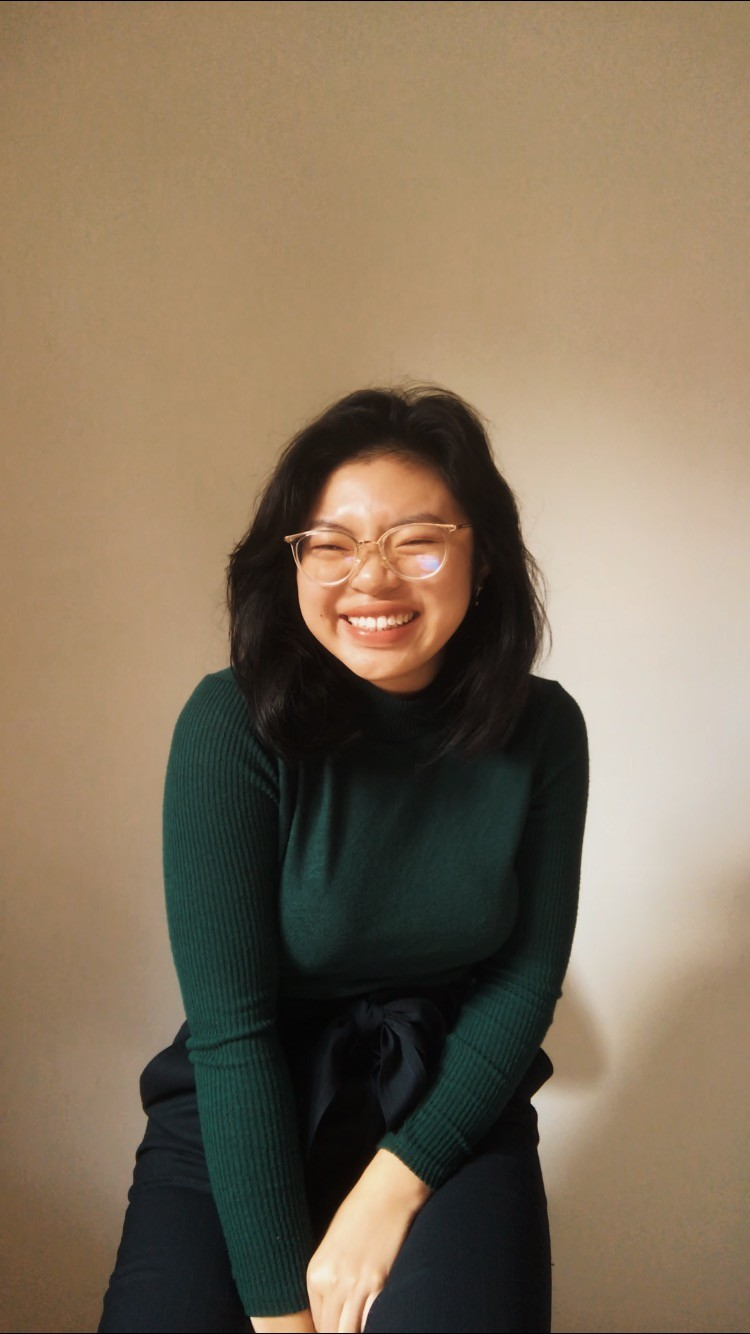 An Asian woman with white framed glasses and a green turtleneck laughing.