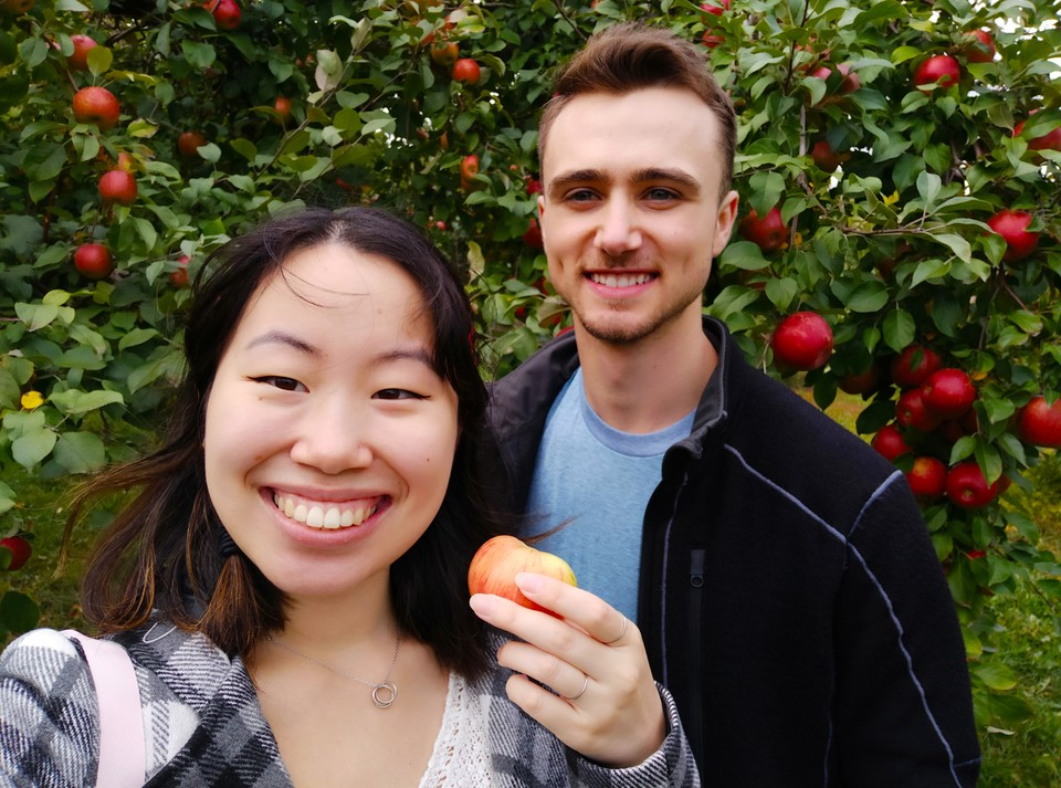 A smiling Asian woman with a man in an apple orchard.