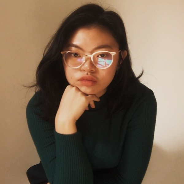 An Asian woman with white framed glasses and a green turtleneck stares directly into the camera.