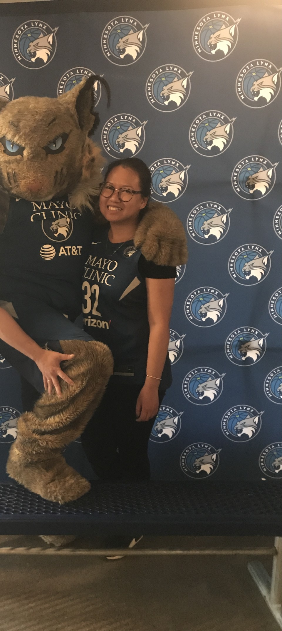 A fox mascot wearing a Mayo Clinic shirt with its arm around a smiling Asian woman.