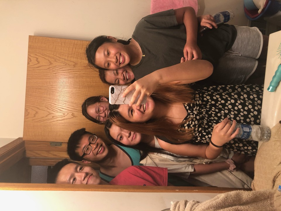 A group of smiling young Asian people taking a bathroom mirror selfie.