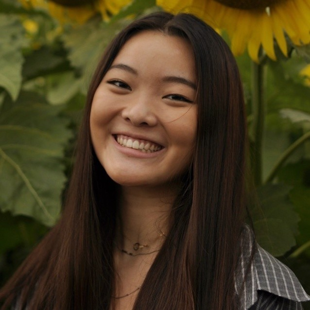 A smiling Asian woman in a sunflower field.