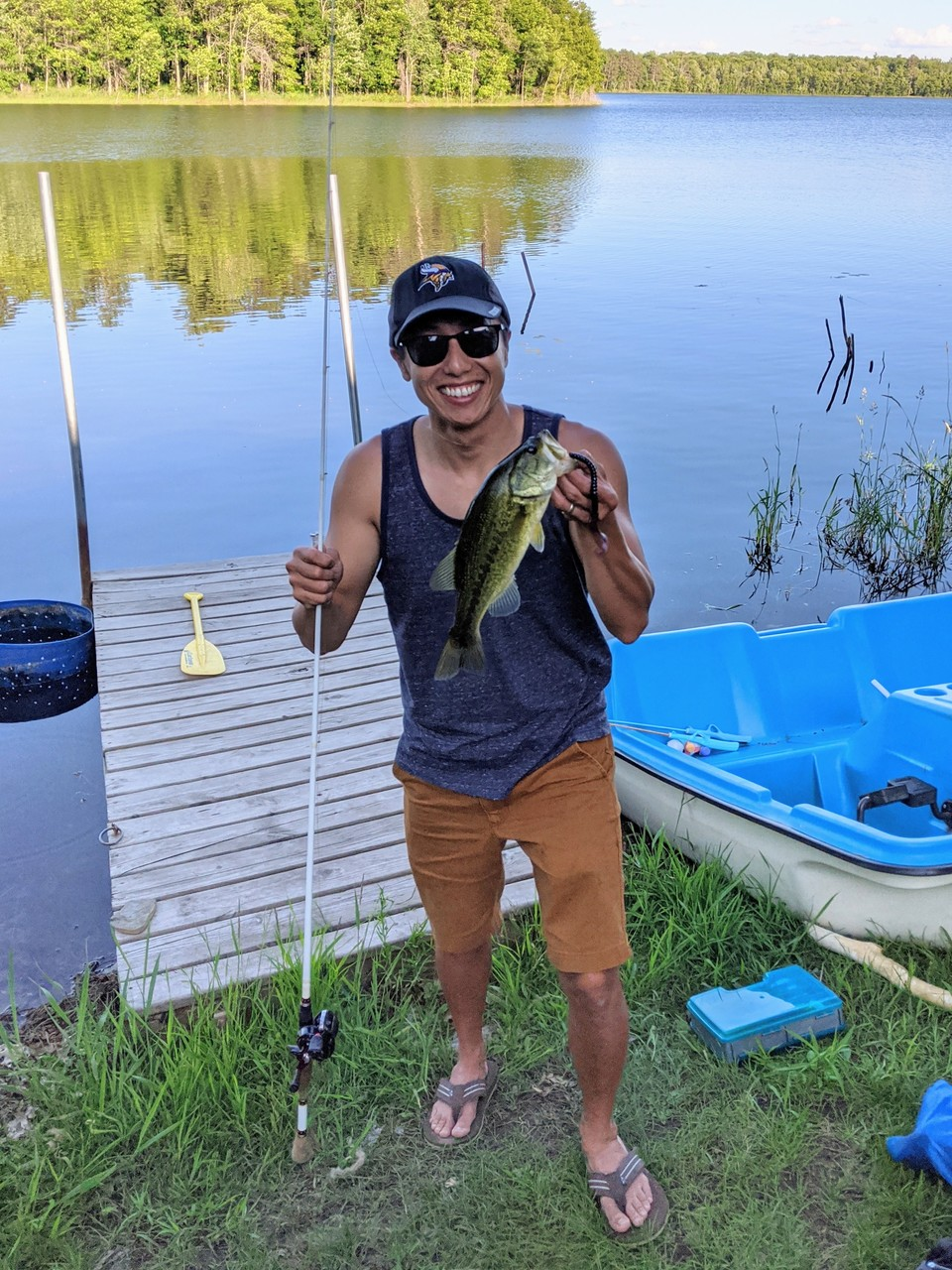 A smiling Asian man holding a fish and standing in front of a lake.