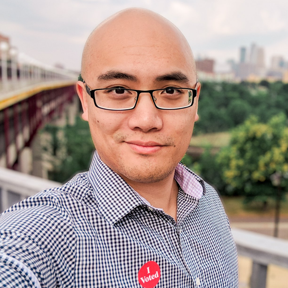 A selfie of a bald Asian man wearing glasses with an 'I voted' sticker on his shirt.