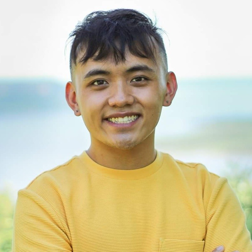 A smiling Asian person wearing a yellow shirt.