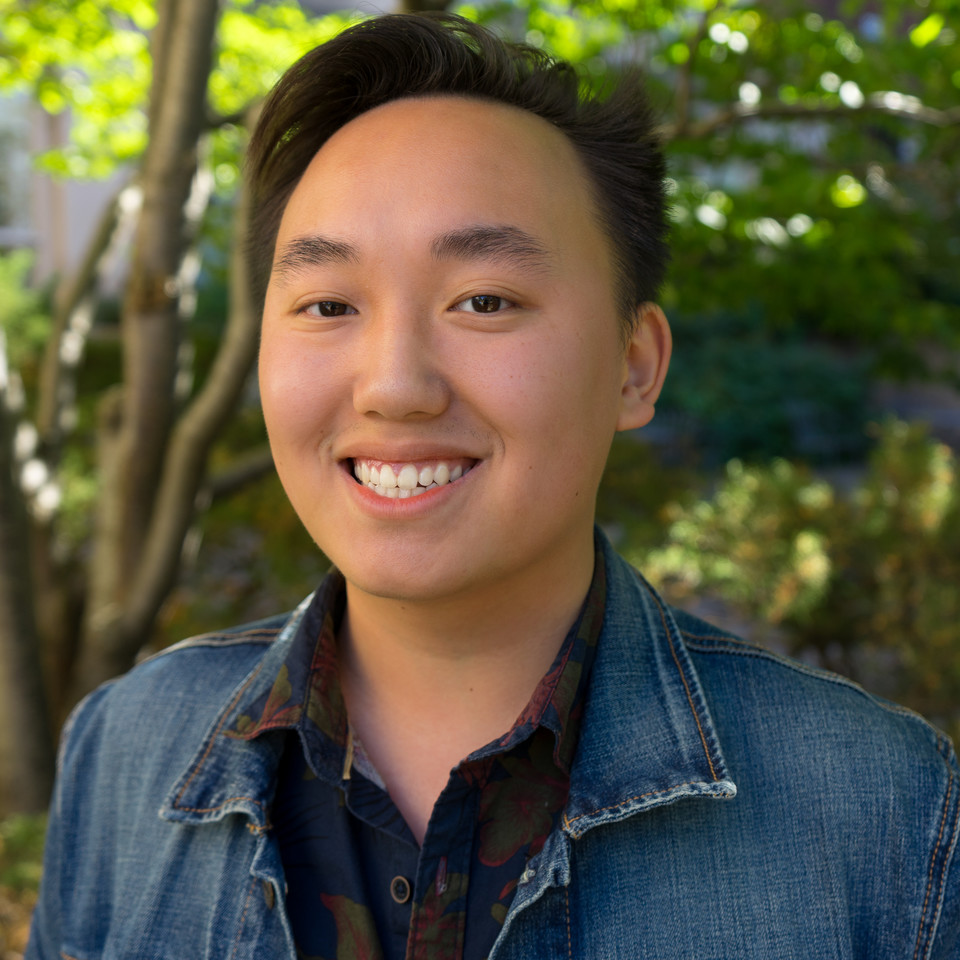 A smiling Asian man with a denim jacket
