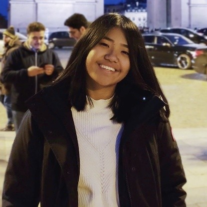 A smiling Asian person wearing a jacket standing outside in front of the Arc de Triomphe in Paris.
