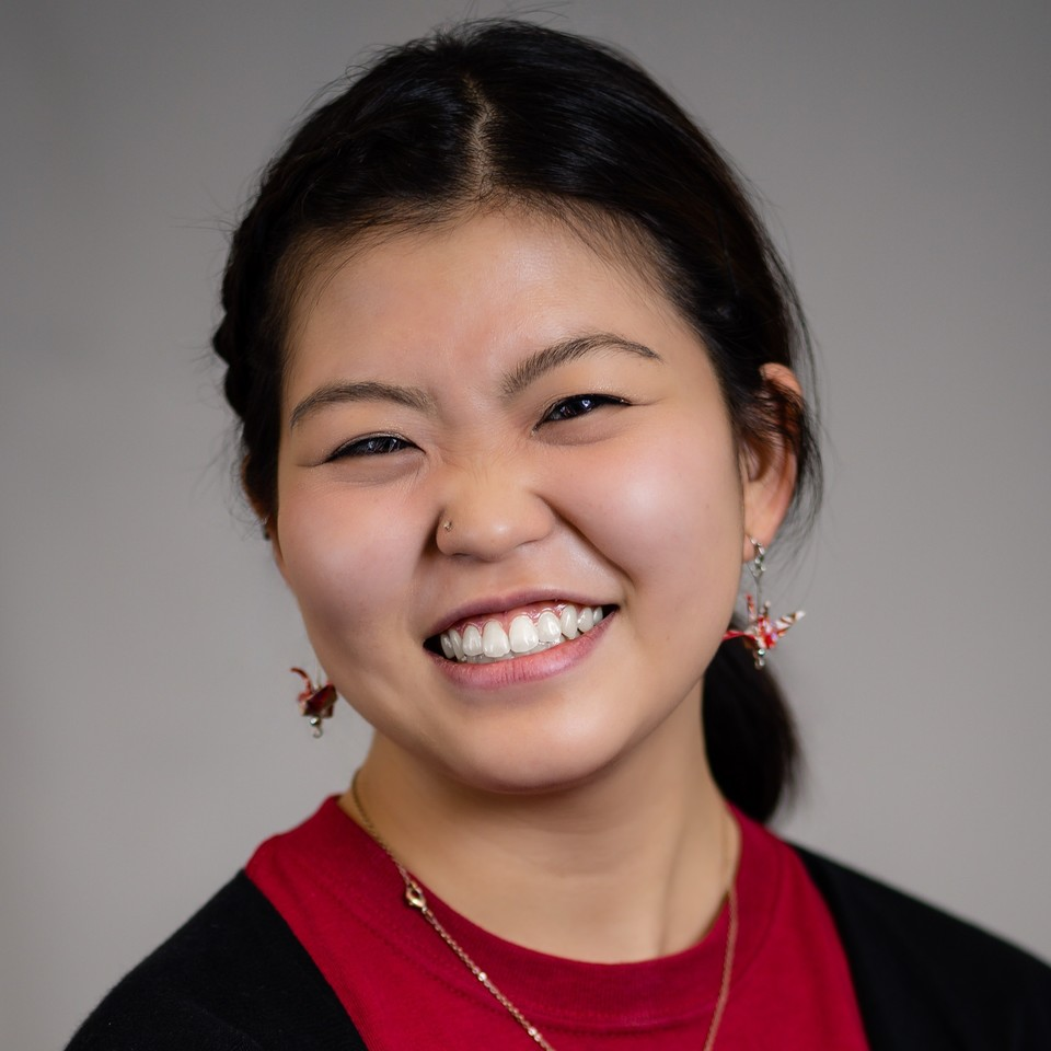 A smiling Asian person with a red shirt and paper crane earrings.